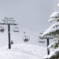 ski areas: chair lift passing snow-covered fir trees at Stevens Pass