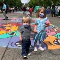 two kids in masks standing on street mural