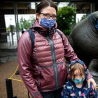 Woman and child wearing masks in front of zoo