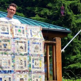 boy displaying handmade quilt