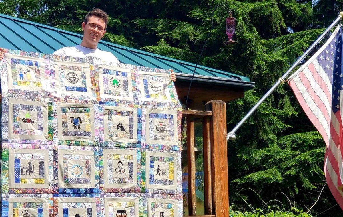 boy displaying handmade quilt