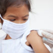 Flu shot: Masked girl getting an injection.