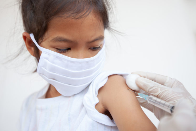 Flu shot: Masked girl getting an injection.