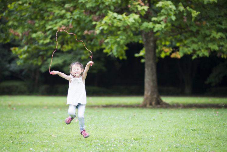 Picks. Girl jumping rope a park.
