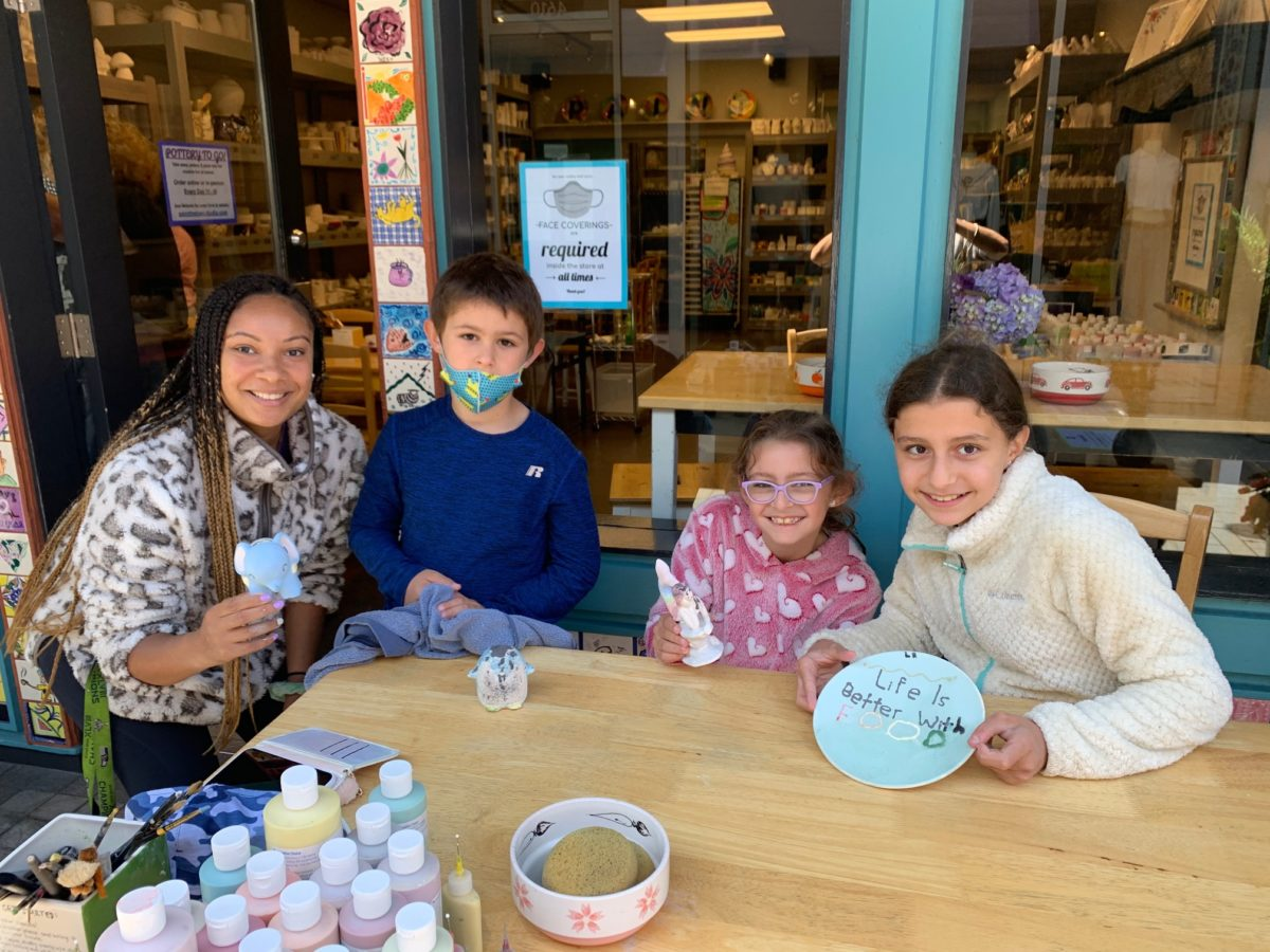 Pottery painting: An adult and three kids show off their creations at the Paint The Town outdoor table