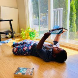 Screen-free days: Child lying on floor reading