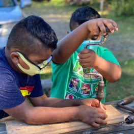 Day trip: boy helps his younger brother with a hand drill