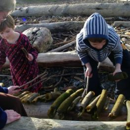 Play outside: grandmother watches two kids play with a xylophone made of kelp