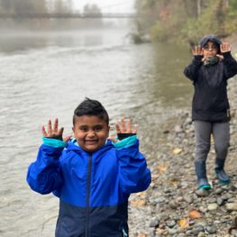 Hikes: two boys in raincoats holding their hands up next to the Snoqualmie river