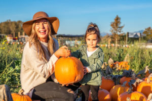 Woman wearing hat and weilding pumpkin, small girl standing next to her in pumpkin patch at Stocker Farms