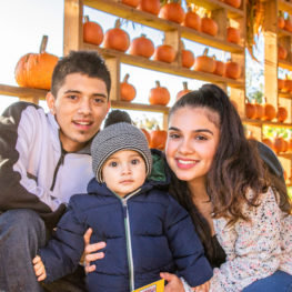 Pumpkin patch: Man, woman and child in front of pumpkins at Stocker Farm