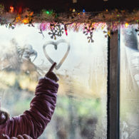 Erika's weekend picks: a girl in a winter coat and hat, drawing a heart in the fogged up window of a train car