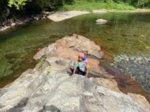 boy on rock in river
