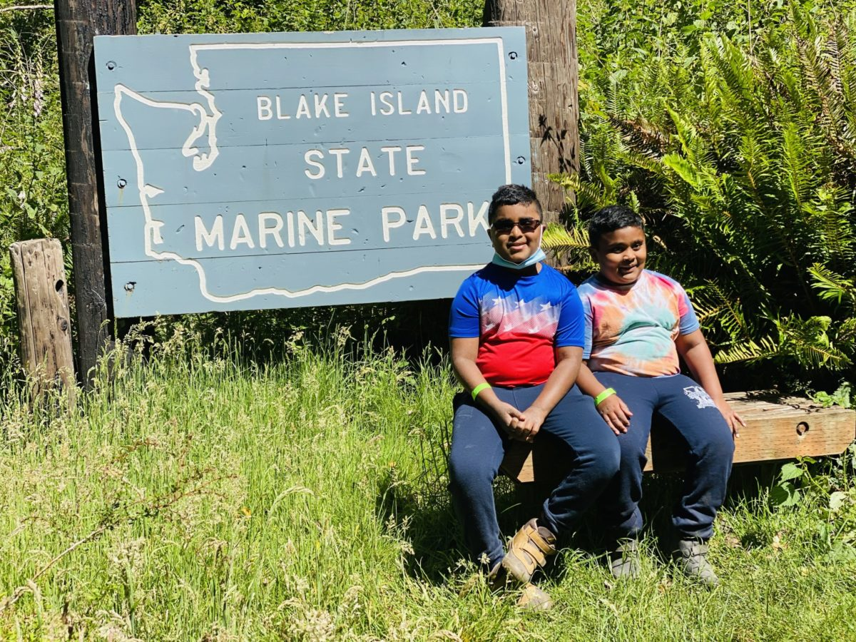 Children seated in front of the Blake Island State Park sign
