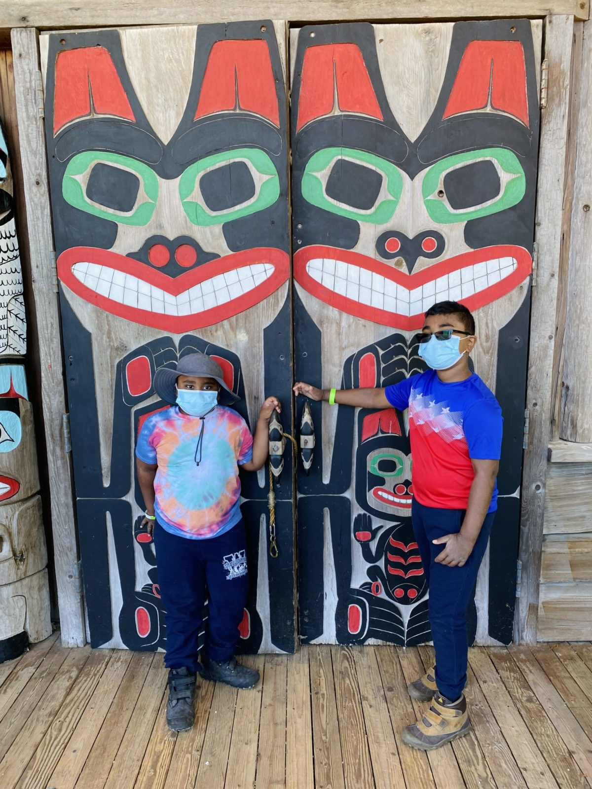 Children in front of large doors adorned with Native American Art