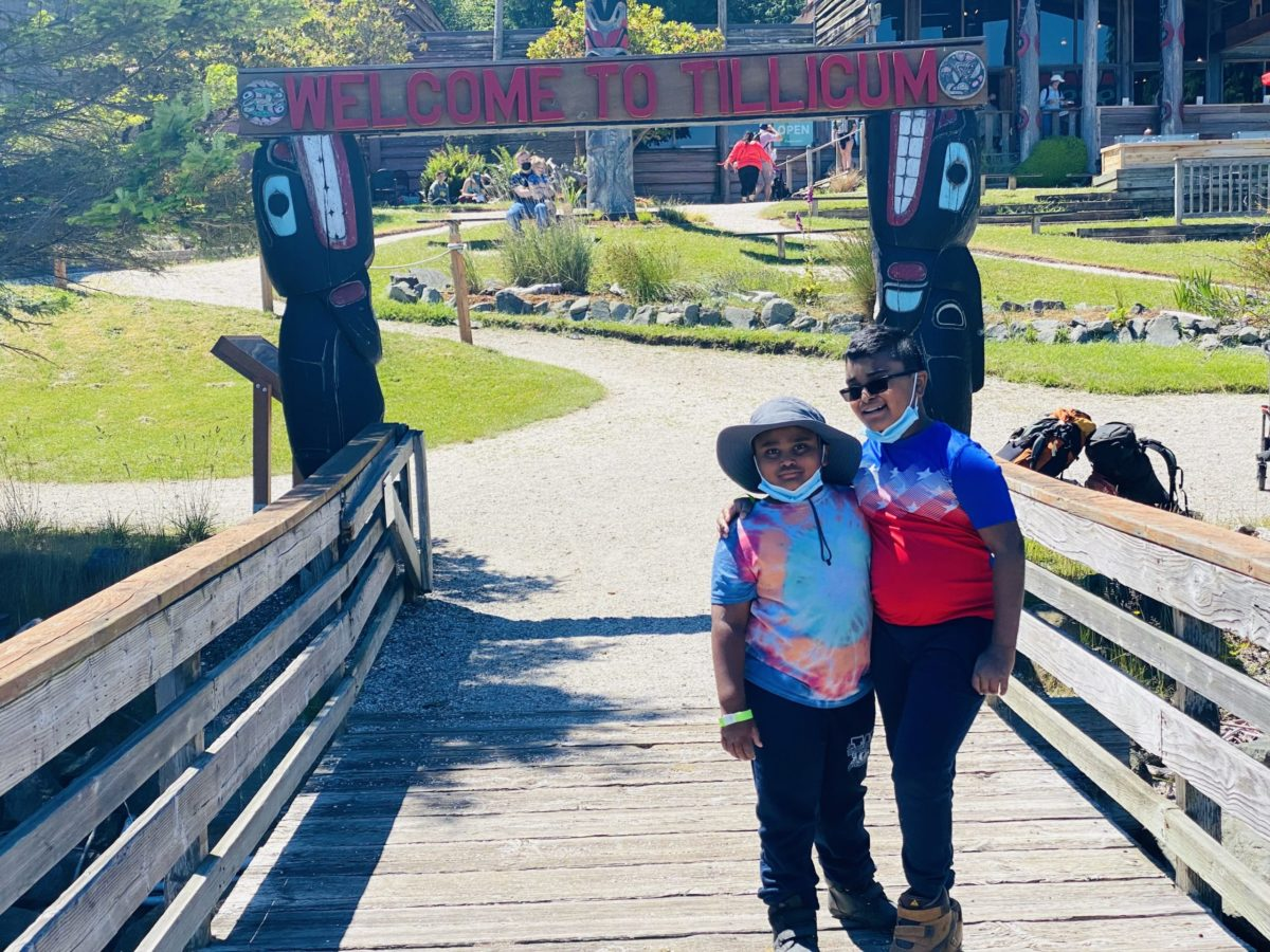 Children stand at the welcome sign at Blake Island